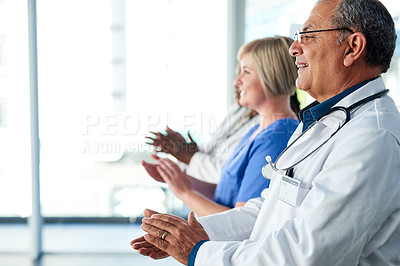 Buy stock photo Cropped shot of a group of medical practitioners applauding while standing in the hospital