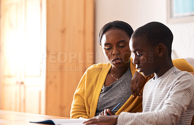 Buy stock photo Cropped shot of a woman helping her young son with his homework