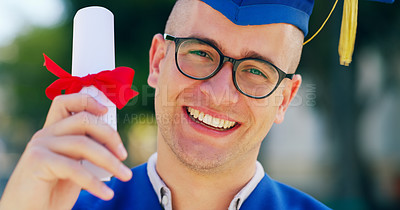 Buy stock photo Cropped portait of a handsome young man standing and holding his degree while being outside during the day