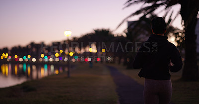 Buy stock photo Cropped shot of a young woman out for a run at nighttime