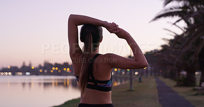 Buy stock photo Rearview shot of a young woman stretching outside before her run