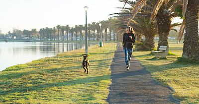 Buy stock photo Shot of a sporty young woman out running with her dog