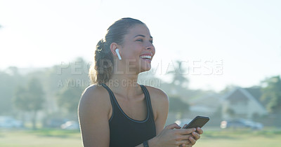 Buy stock photo Cropped shot of a sporty young woman wearing earphones and using her cellphone while out for a run