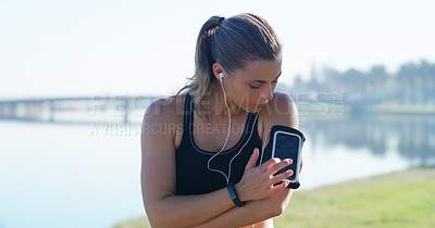 Buy stock photo Shot of a young woman selecting a playlist on her device before her run