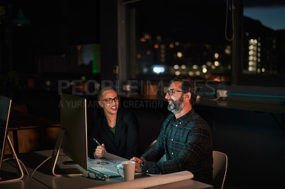 Buy stock photo Cropped shot of two businesspeople sitting and working on a computer while in their office late at night