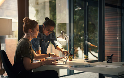 Buy stock photo Shot of two young coworkers using a laptop during a late night at work