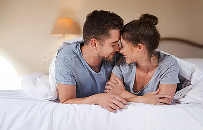 Buy stock photo Shot of an affectionate young couple spending some quality time together in their bedroom at home