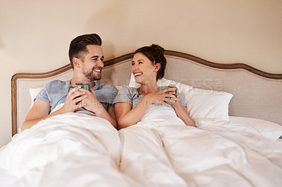 Buy stock photo Shot of a happy young couple drinking coffee in bed in their bedroom at home