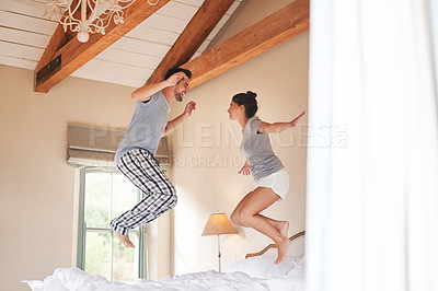 Buy stock photo Full length shot of a cheerful young couple playing and jumping on their bed in their bedroom at home