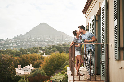 Buy stock photo Full length shot of an affectionate young couple drinking coffee while standing on their balcony at home in the morning