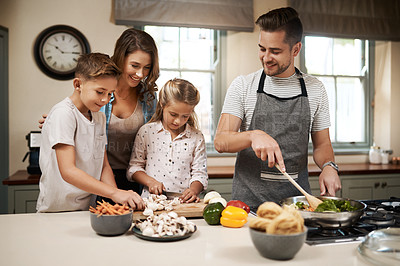 Buy stock photo Cropped shot of a young family cooking in the kitchen