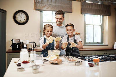 Buy stock photo Shot of a man and his two children baking in the kitchen at home