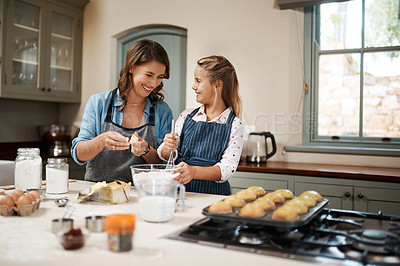 Buy stock photo Shot of a woman and her daughter baking together in the kitchen