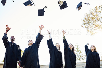 Buy stock photo Shot of a group of graduates  throwing their hats in the air