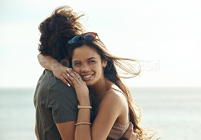 Buy stock photo Cropped portrait of an affectionate young couple hugging each other while standing on the beach during a road trip