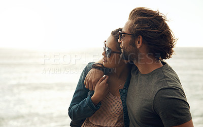 Buy stock photo Cropped shot of an affectionate young couple holding each other on the beach during a road trip