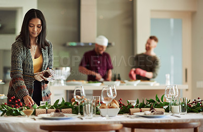 Buy stock photo Shot of two young woman setting the table at home in preparation for a Christmas gathering