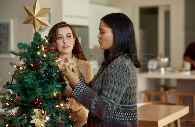 Buy stock photo Shot of two young women decorating a christmas tree at home