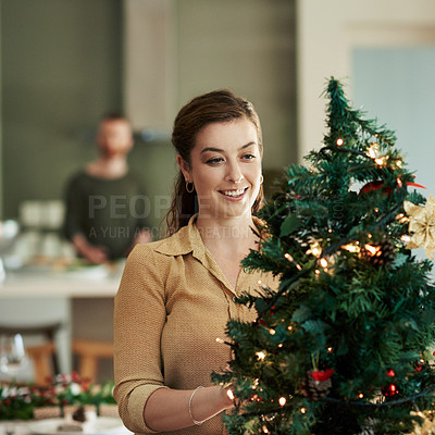 Buy stock photo Shot of a young woman decorating a christmas tree at home with her husband in the background