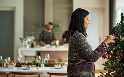 Buy stock photo Shot of a young woman decorating a christmas tree at home with her friends in the background