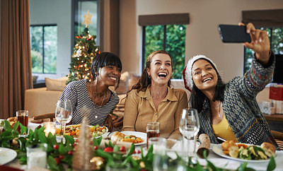 Buy stock photo Shot of a group of young women taking a selfie while having Christmas lunch at home