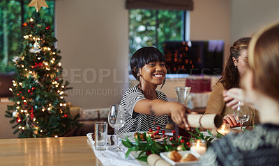 Buy stock photo Shot of young friends pulling a cracker while having Christmas lunch at home
