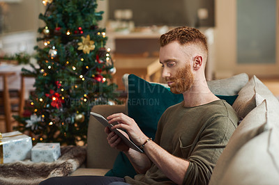 Buy stock photo Shot of a young man using a digital tablet on the sofa at home during Christmas