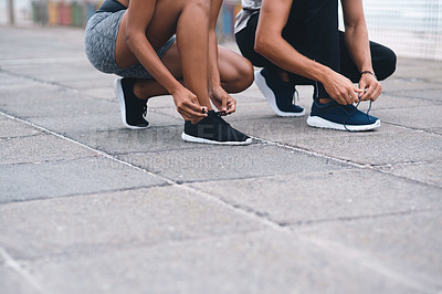 Buy stock photo Closeup shot of two unrecognisable people tying their laces while exercising outdoors