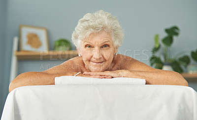 Buy stock photo Cropped portrait of a smiling senior woman lying down on a massage bed before her massage during the day