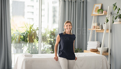Buy stock photo Cropped portrait of an attractive mature masseuse smiling and standing by a massage bed in the spa during the day
