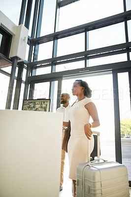 Buy stock photo Shot of a happy young couple walking in with their luggage and checking in at the reception of a hotel