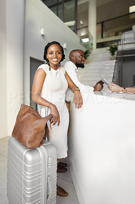 Buy stock photo Portrait of a beautiful young woman checking in with her husband at the reception of a hotel