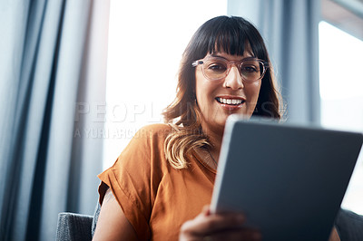 Buy stock photo Shot of a young woman using a digital tablet while relaxing at home