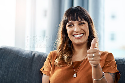 Buy stock photo Shot of a young woman showing thumbs up while relaxing at home