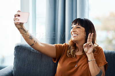 Buy stock photo Cropped shot of a young woman taking selfies while relaxing at home