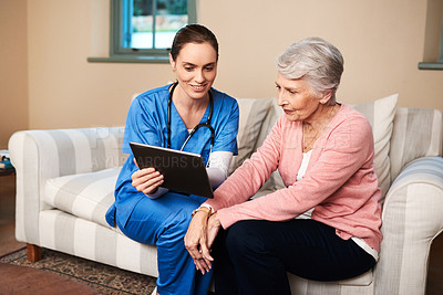 Buy stock photo Shot of a female nurse showing her senior patient something on a digital tablet