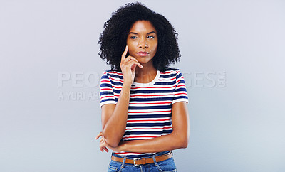 Buy stock photo Studio shot of an attractive young woman looking thoughtful against a grey background