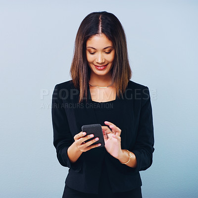 Buy stock photo Studio shot of a beautiful young businesswoman using a smartphone against a grey background