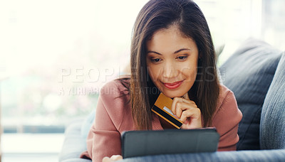 Buy stock photo Cropped shot of an attractive young woman using a tablet for online shopping while lying down on the sofa