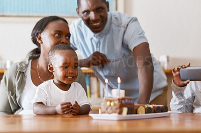 Buy stock photo Cropped shot of a cheerful young family celebrating their little toddler son's birthday with cake at home during the day