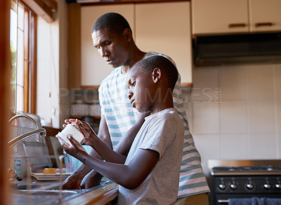 Buy stock photo Cropped shot of a cheerful young man and his son washing dishes together in the kitchen at home