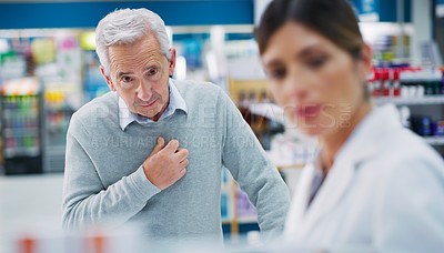 Buy stock photo Shot of a pharmacist assisting a customer in a chemist