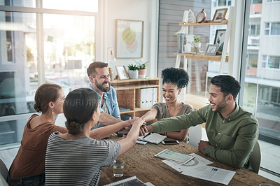 Buy stock photo Shot of a group of young businesspeople joining hands during a meeting in a modern office
