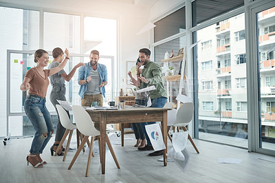 Buy stock photo Shot of a group of young businesspeople celebrating during a meeting in a modern office