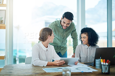 Buy stock photo Shot of a group of businesspeople working together on a digital tablet in an office