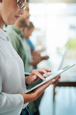 Buy stock photo Shot of a young businesswoman using a digital tablet while standing in line with her colleagues in an office