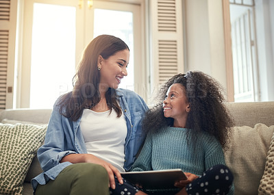 Buy stock photo Shot of young girl using a digital tablet while sitting at home with her mother