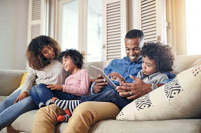Buy stock photo Cropped shot of a young family relaxing on the sofa at home