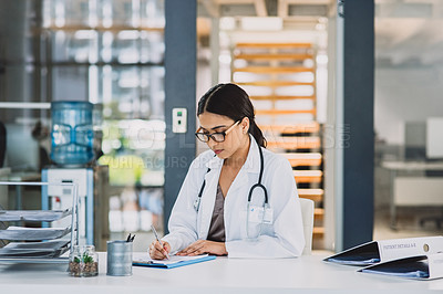 Buy stock photo Cropped shot of an attractive young doctor sitting and writing on a clipboard while in her office during the day