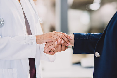Buy stock photo Cropped shot of an unrecognizable doctor holding the hand of an unrecognizable patient while indoors during the day